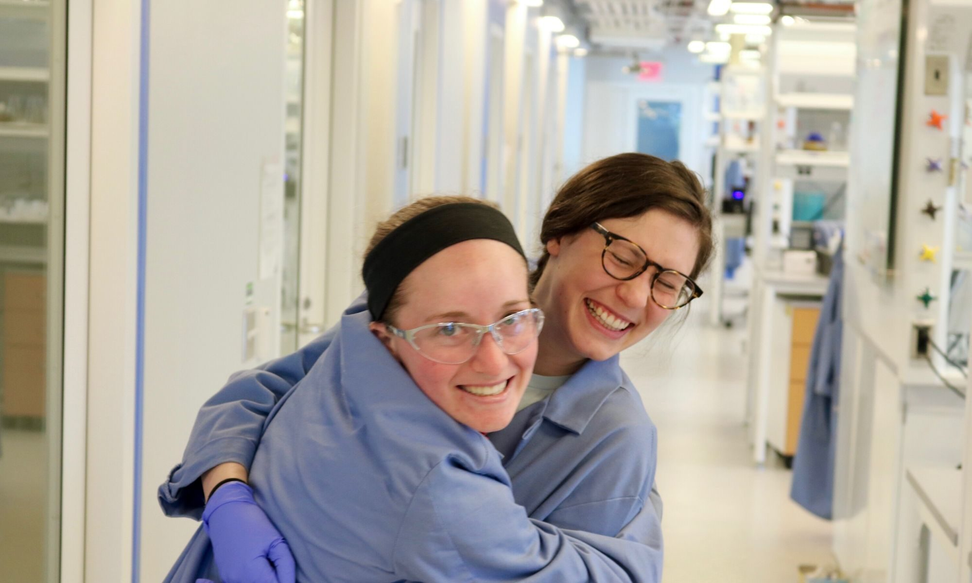 Two women chemists smile and embrace in a lab setting.